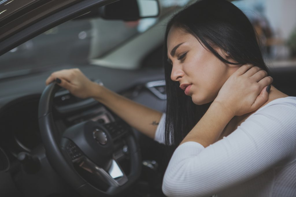 Female driver rubbing her aching neck after accident