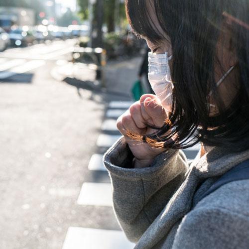girl coughing through mask